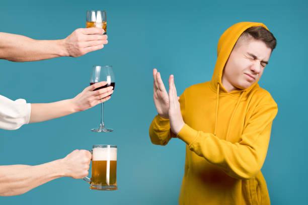 Adolescente con una sudadera amarilla rechaza diferentes tipos de alcohol - foto de stock