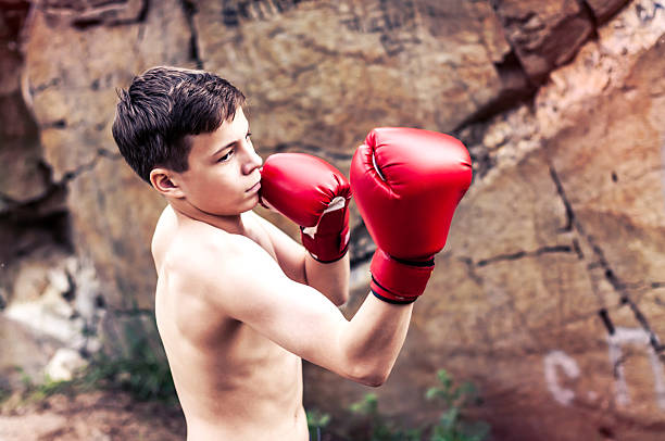 Teenager in boxing gloves near the cliff stock photo
