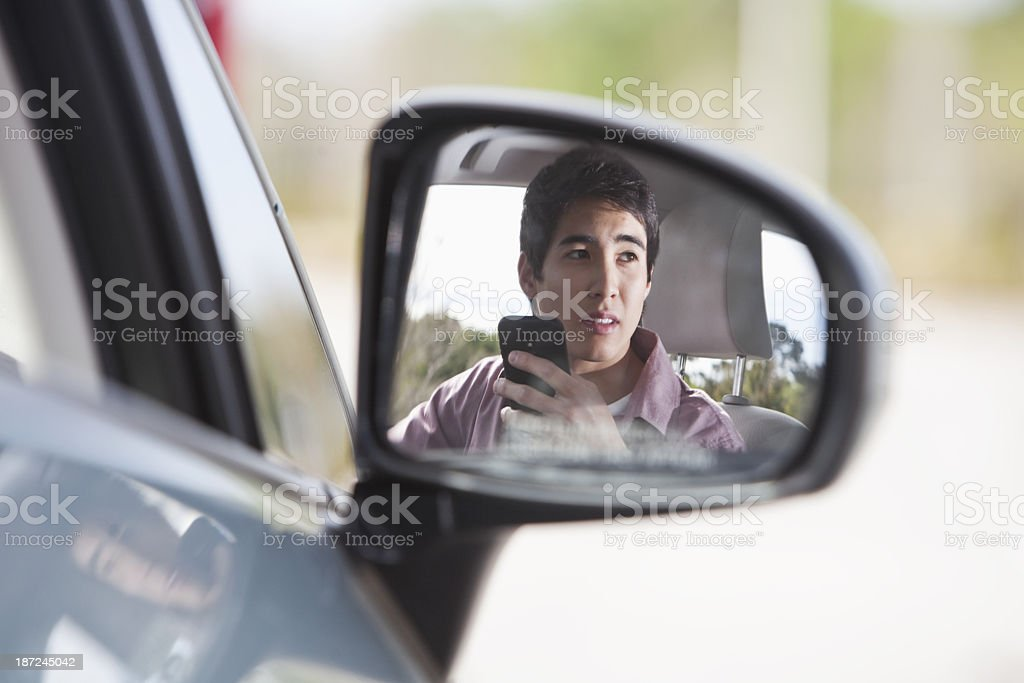 Teenager in car using mobile phone stock photo