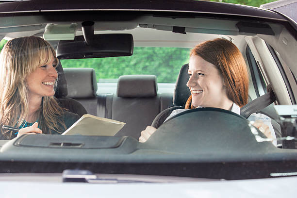 Teenager in car with driving instructor Teenager in car with driving instructor driving instructor stock pictures, royalty-free photos & images
