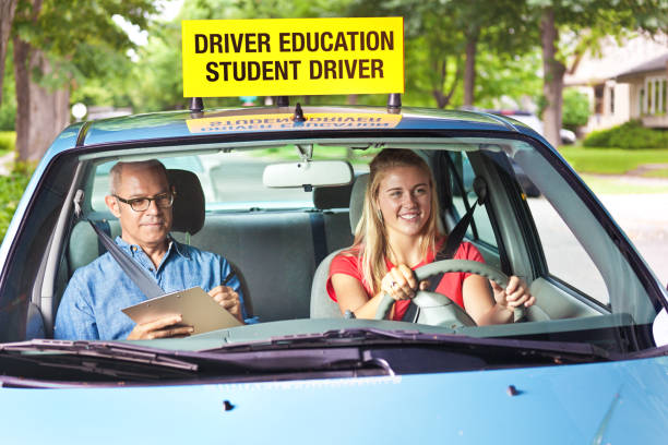 Teenager in Drivers's License Exam with Examiner in Car A young Caucasian teenage girl in her driver's license exam session. She is driving a vehicle with an examiner sitting on the passenger seat. driving instructor stock pictures, royalty-free photos & images