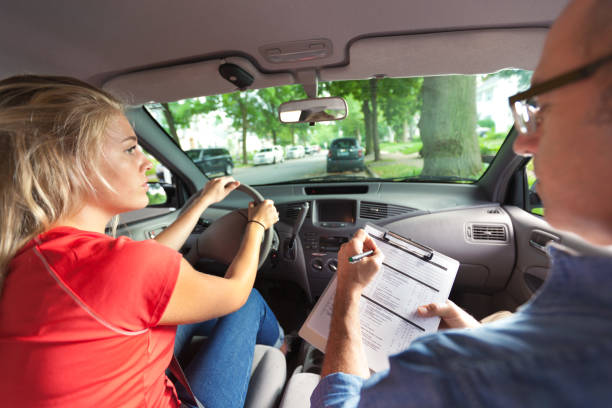 Teenager in Drivers's License Exam with Examiner in Car +++NOTE TO INSPECTOR+++ The paper form on clipboard is a prop created for the photo shoot. driving instructor stock pictures, royalty-free photos & images