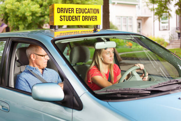 Teenager in Drivers's License Exam with Examiner or Instructor in Car A young Caucasian teenage girl learning to drive with an instructor or she is in her driver's license exam session. She is driving a vehicle with an examiner sitting on the passenger seat. driving instructor stock pictures, royalty-free photos & images