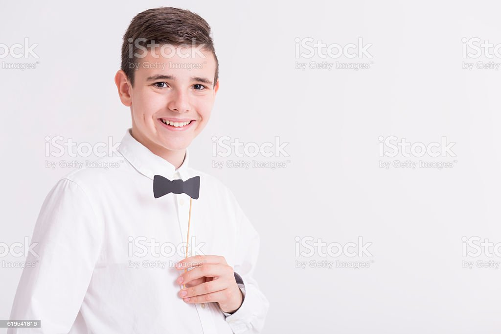Teenager in elegant white shirt with paper dicky bow stock photo