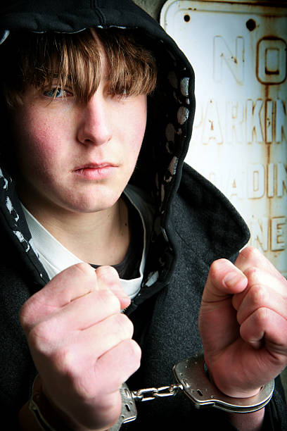 teenager in handcuffs - boy handcuffs stock pictures, royalty-free photos & images