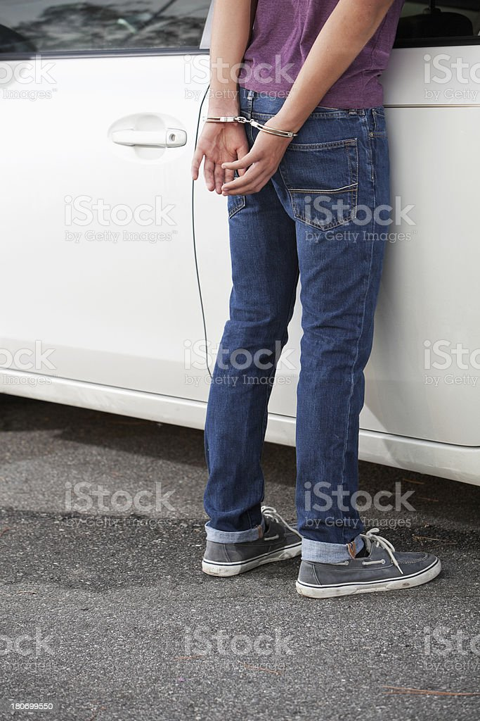 Teenager in handcuffs stock photo