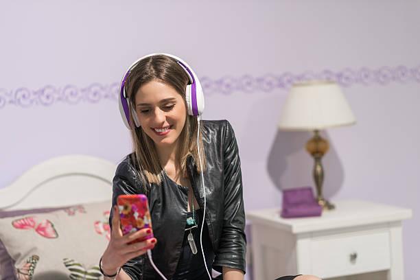 teenager in der ihrem schlafzimmer beim musikhören mit smartphone - lila teenschlafzimmer stock-fotos und bilder