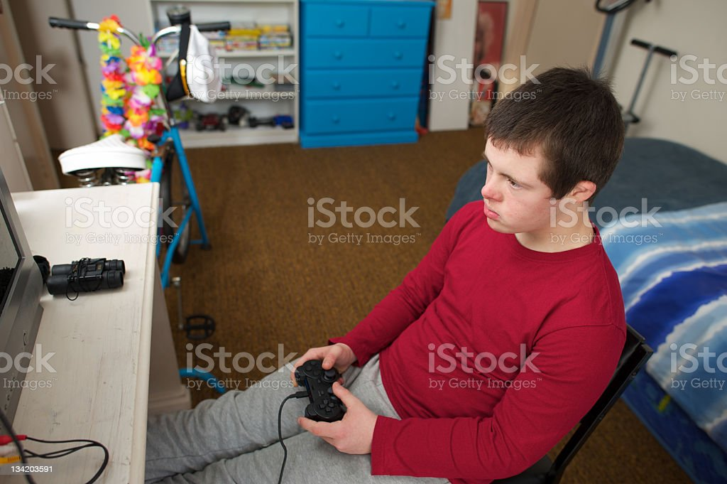 Teenager in his bedroom playing a video game stock photo