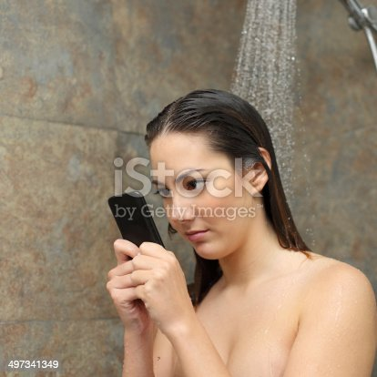 istock Teenager in the shower obsessed with the smart phone 497341349