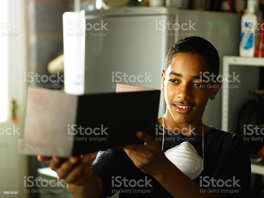 Teenager inspecting woodwork project royalty free stockfoto
