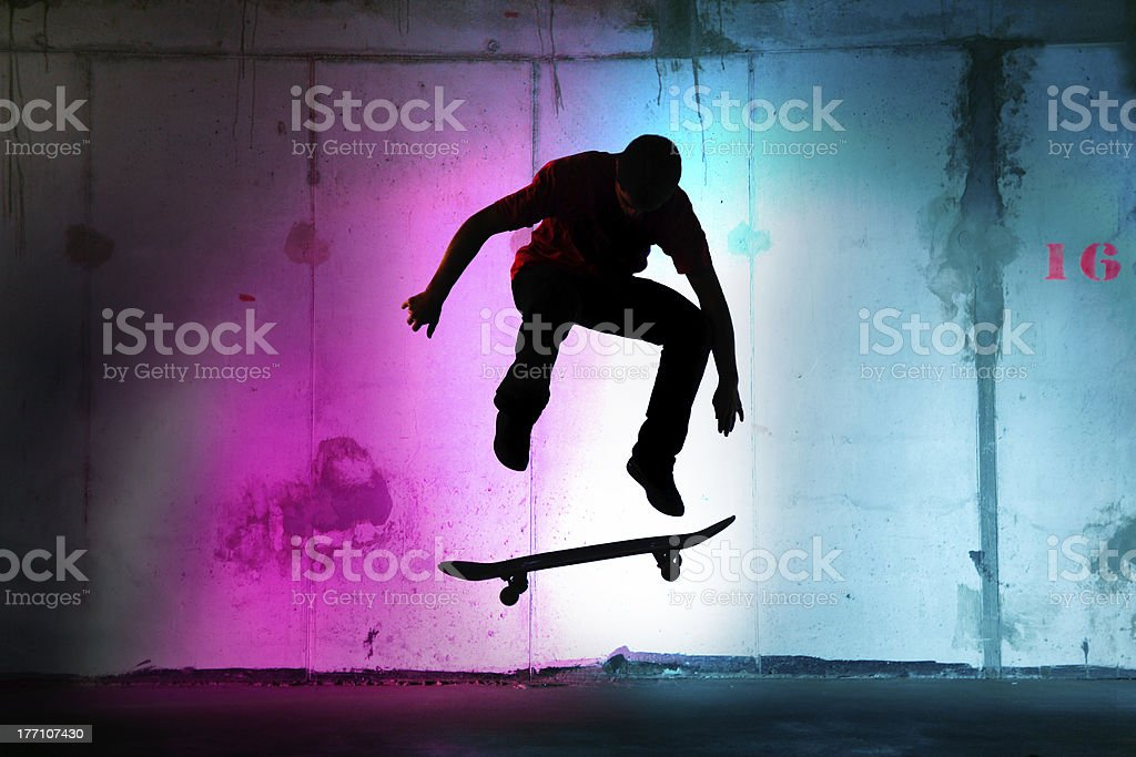 teenager jumping, skateboarding at night black silhouette stock photo