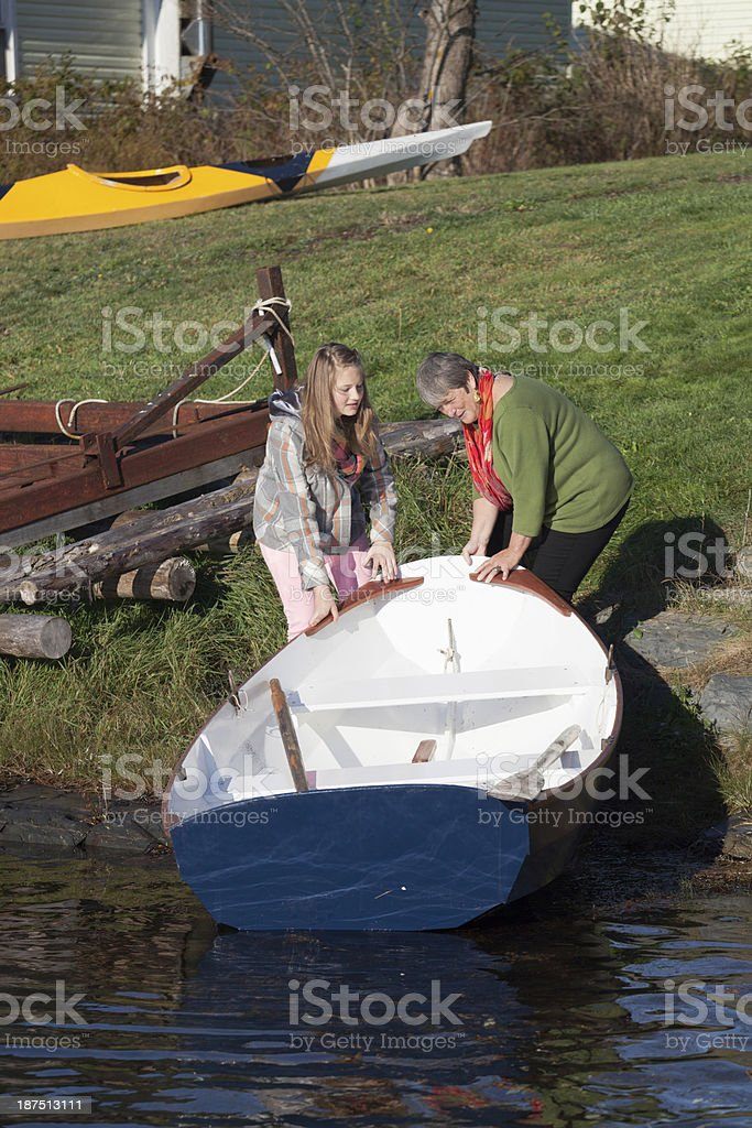 teenager launches rowboat with help from active grandmother royalty-free stock photo