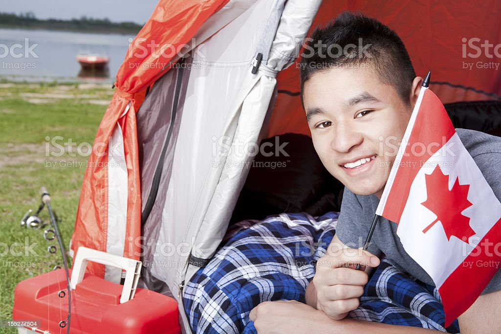 Teenager laying while holding the Canada flag royalty-free stock photo