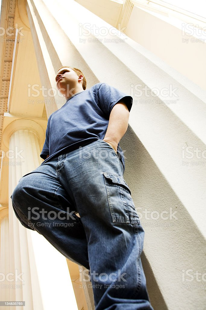 Teenager leaning against column of home viewed from below. royalty-free stock photo