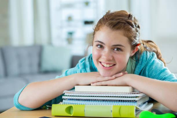 teenager stützt sich auf einen stapel bücher - haushaltsbuch führen stock-fotos und bilder