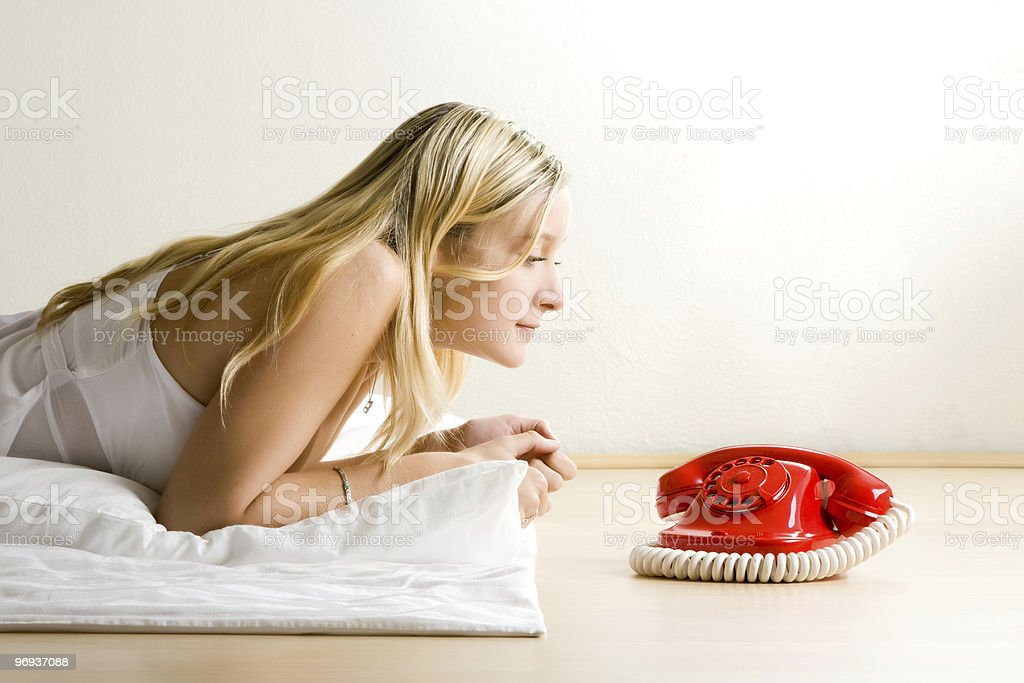 Teenager looking at red phone royalty-free stock photo