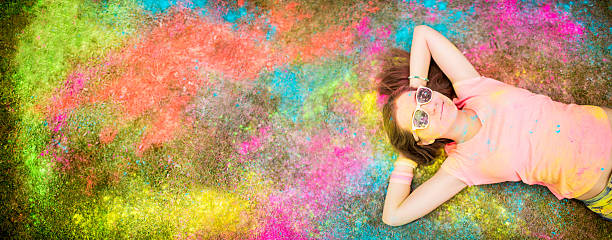Teenager lying on holi powder covered festival ground Smiling hipster at holi festival with lots of copy space colored powder stock pictures, royalty-free photos & images
