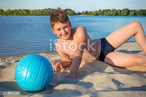 A teenager lying on the beach with a ball on a sunny day against the background of the river, a close-up.
