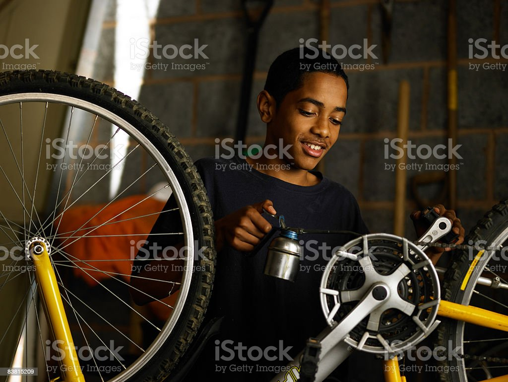 Teenager oiling bicycle chain royalty-free stock photo