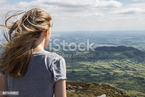 Teenager (girl) on a vantage point (Slieve Gullion, County Armagh), looking across an Irish rural landscape, stretching from County Armagh (Northern Ireland, UK) across to County Louth (Republic of Ireland).  The open border between the United Kingdom and Republic of Ireland winds its way through fields, villages, farmsteads and along roads for 310 miles (499 km).