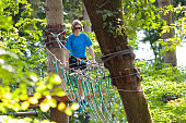 Teenager in forest adventure park. Teen age boy on high rope trail. Agility and climbing outdoor amusement center for children and young adults. Extreme outdoor sport. Jungle rope way with zip line.