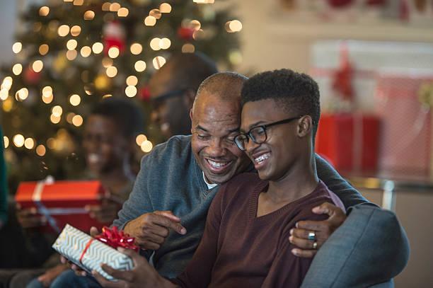 teenager opening a present - geschenke eltern weihnachten stock-fotos und bilder