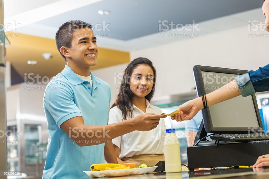 Teenager paying for school lunch with card in lunchroom stock photo