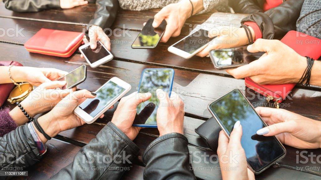 Les adolescents ayant l'amusement utilisant des smartphones-la communauté millénaire partageant le contenu sur le réseau de médias sociaux avec les téléphones intelligents mobiles-concept de technologie avec le jeu millénaire avec des dispositifs de photo libre de droits