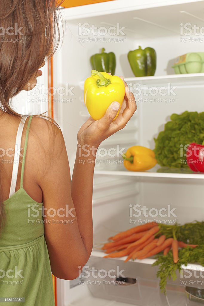 Teenager picking holding a yellow bell pepper in her hands royalty-free stock photo
