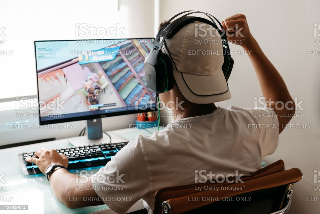 Teenager playing Fortnite video game on PC stock photo