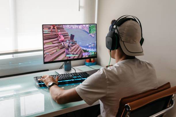 teenager playing fortnite video game on pc - esports stock photos and pictures