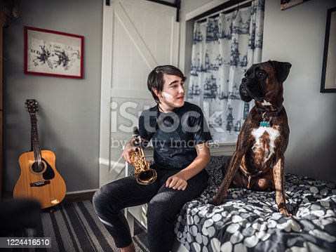 Teenage boy enjoying his hobby: He is  in his bedroom playing alto saxophone. His boxer dog is keeping him company while practicing mellow jazz tunes.