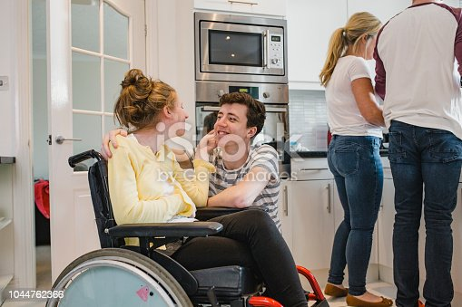 Teenage boy is relaxing at home with his disabled sister who is in a wheelchair while his parents prepare food.