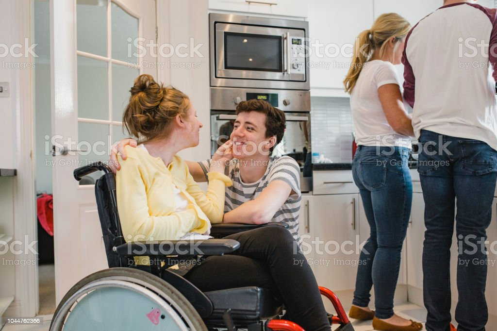 Teenager Playing with Disabled Sister at Home stock photo