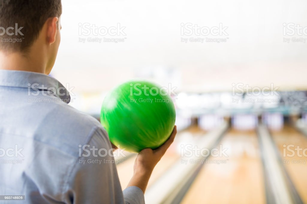 Rear view of teenager playing with green bowling ball in club