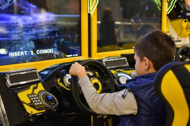 teenager spielt auf dem gaming-maschine simulator auto im club - arkade stock-fotos und bilder