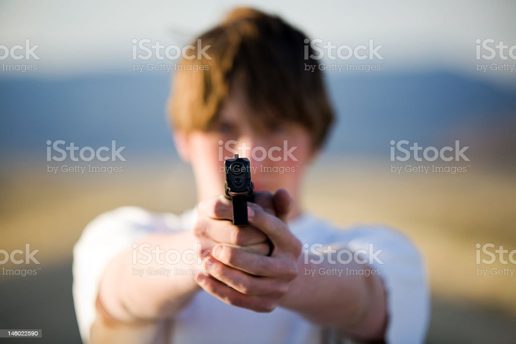 teenager pointing handgun at camera royalty-free stock photo