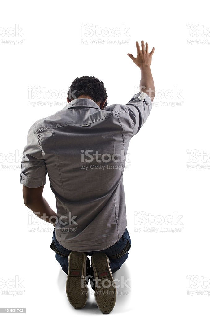 Teenager praying on his knees stock photo