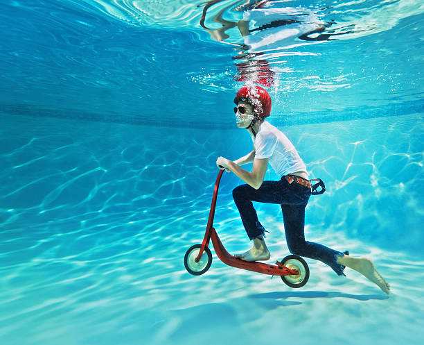 teenager pushing a scooter underwater - bisarr bildbanksfoton och bilder