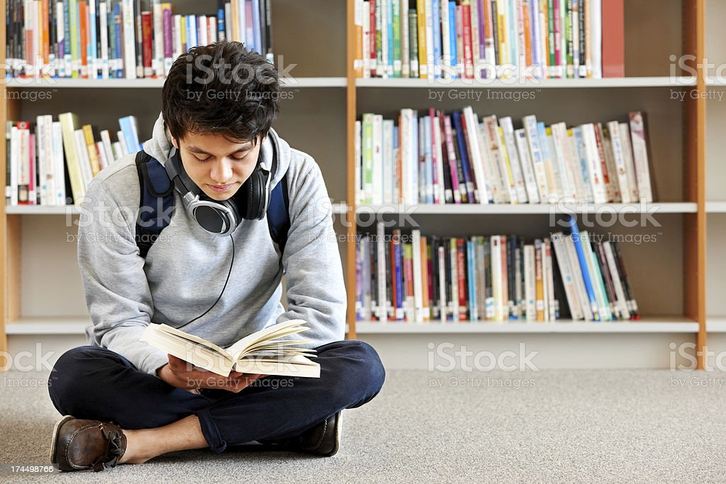 Teenager reading a book in the library royalty-free stock photo