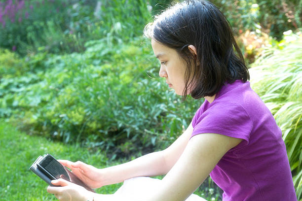 Teenager reading on a kindle stock photo