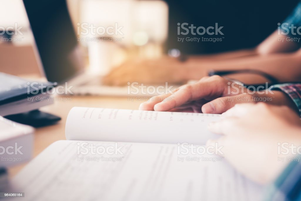 Teenager reading textbook in library. - Royalty-free Adult Stock Photo