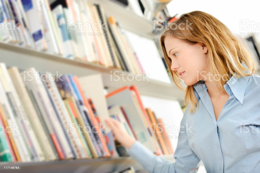 Teenager searching a book in the library royalty-free stock photo