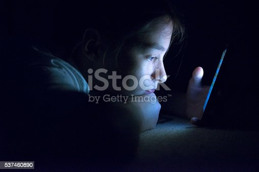 Teenager sending email from smart phone in her bed, Typing text message on smartphone. young cell phone addict teen  awake at night in bed using smartphone for chatting