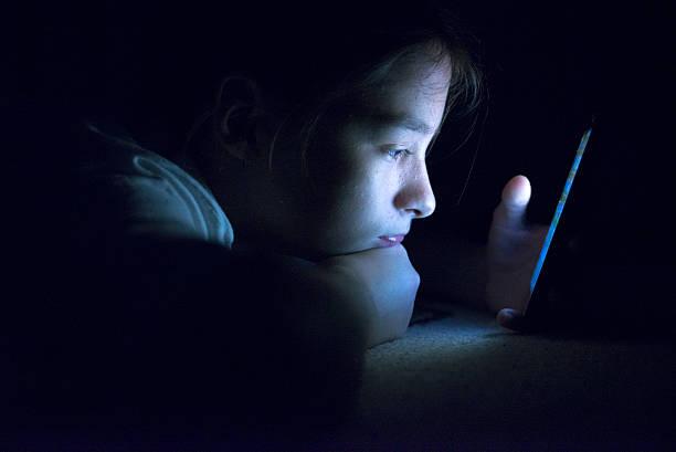 adolescente, l'invio di e-mail da uno smartphone nel suo letto - assuefazione foto e immagini stock