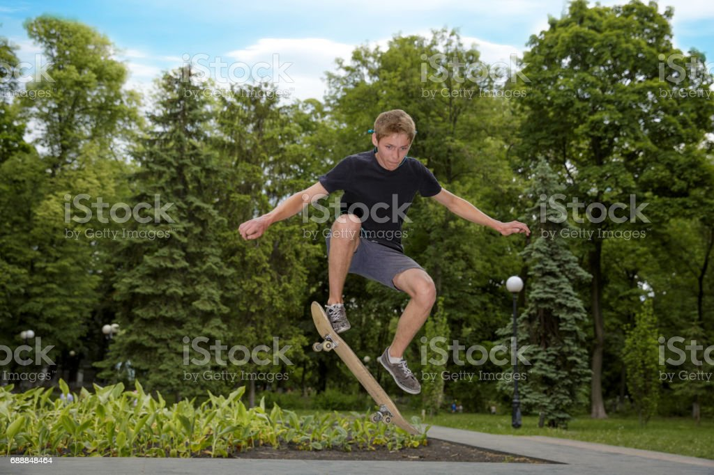 teenager shot in the air on a skateboard in a skate park stock photo