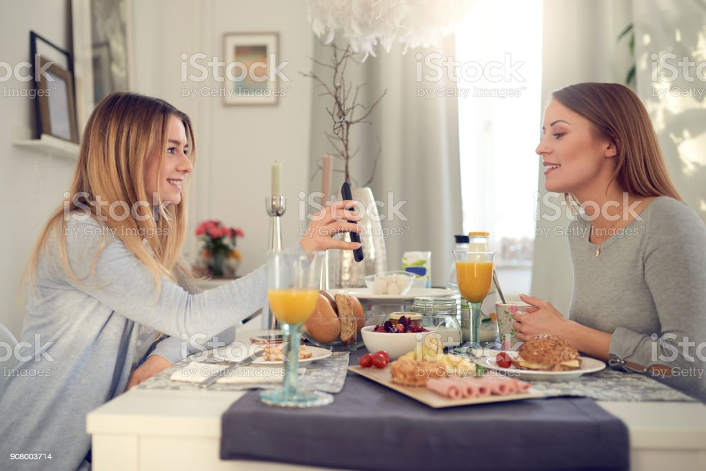 Teenager showing her mother her mobile phone stock photo