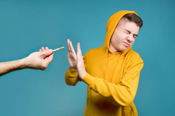 adolescente muestra disgusto cuando sostienen un cigarrillo - foto de stock