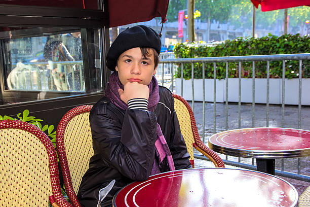 Teenager sitting at cafe on the Champs Elysees, Paris stock photo