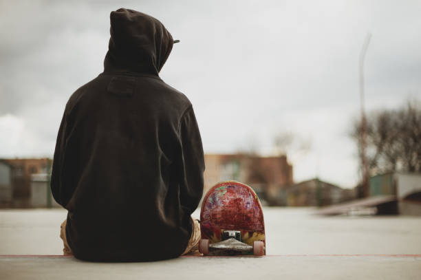 Teenager sitting in a black sweatshirt holding a skateboard on a slum background urban stock photo